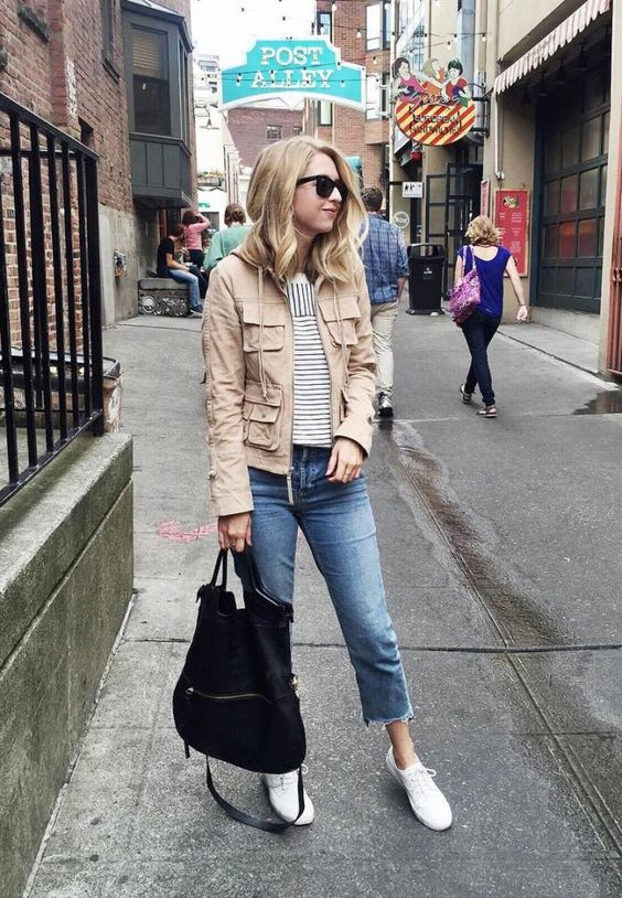 a tan cargo jacket, a striped tee, blue cropped jeans, white sneakers and a black tote bag