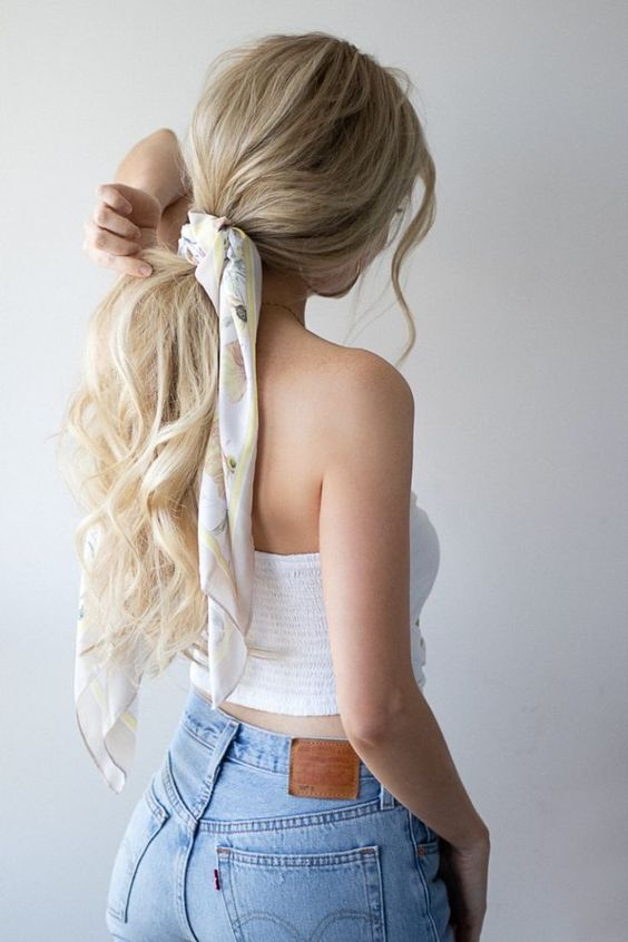 a low ponytail with waves and locks down accented with a colorful hair tie is a nice idea for a girlish touch
