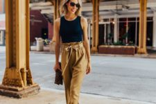 15 a summer look with a black sleeveless top, mustard paper bag pants, black heels and an animal print clutch