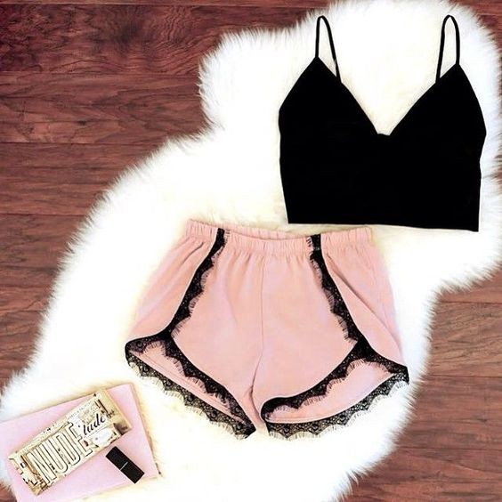 pink shorts with a black lace trim and a black crop top is a sexy combo to wear right now