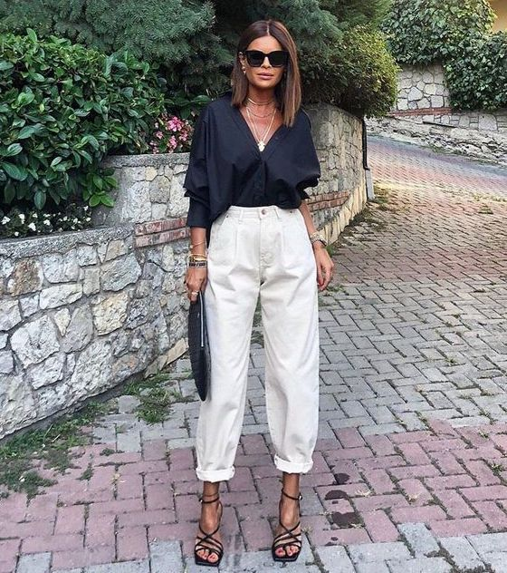 a trendy summer look with a black blouse, white slouchy pants, black strappy shoes and a black clutch