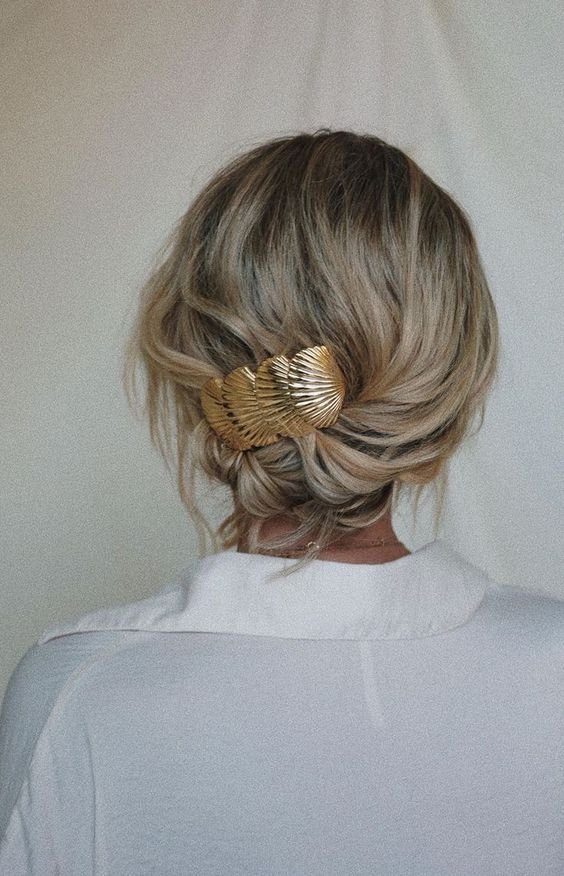 a wavy low updo secured with a pretty gold barrette, which is a hot trend for now