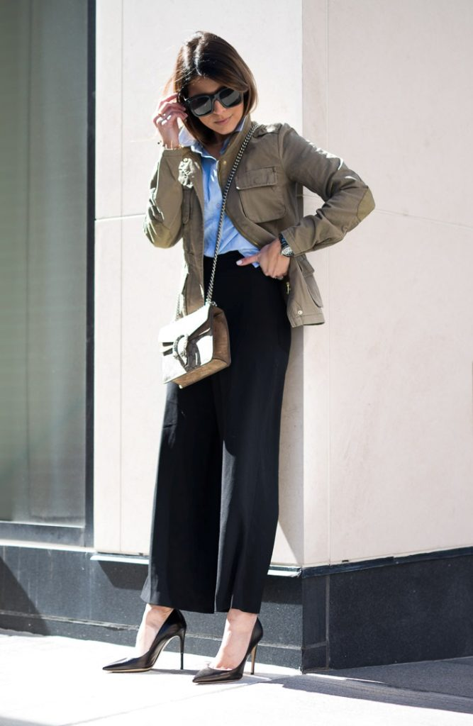 an office look with a blue shirt, black pants, black heels, a tan cargo jacket, a neutral crossbody bag