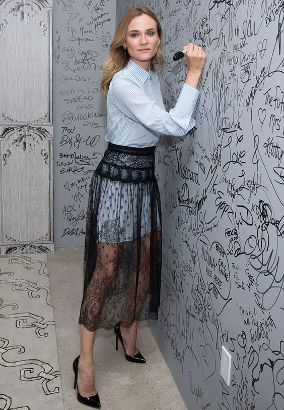 Diane Kruger wearing a blue striped shirtdress, a black lace sheer midi skirt, black heels