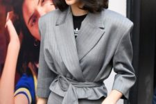 Kendall Jenner wearing a grey pansuit with a cropped blazer with a sash and a printed tee