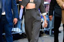 Kristen Stewart rocking a grey pantsuit with a cropped blazer and a catchy bra plus black shoes