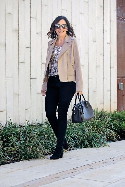With beige jacket, black leather bag, black pants and heeled boots