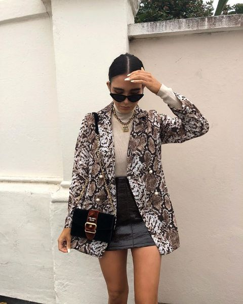 With beige turtleneck, black leather mini skirt and marsala chain strap bag