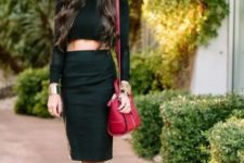 With black cropped top, red bag and high heels