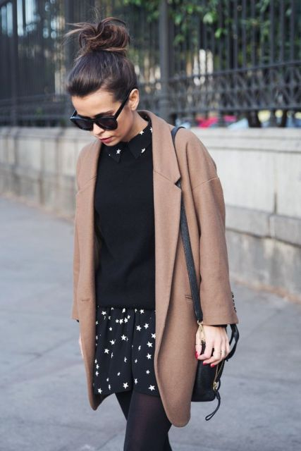 With black sweater, brown coat and black bag