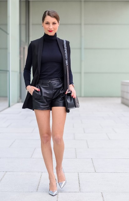 With black turtleneck, black vest, leather shorts and chain strap bag