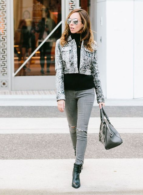 With black turtleneck, distressed jeans, black embellished bag and black ankle boots