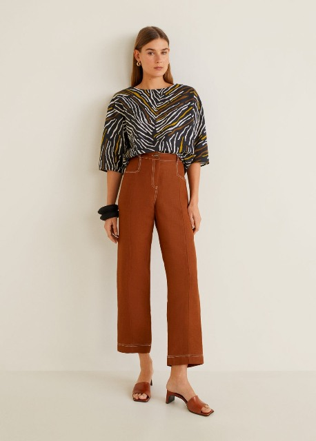 With brown cropped trousers and brown mules