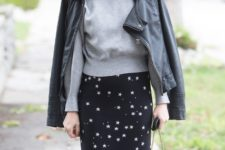 With gray sweater, black leather jacket and black chain strap bag