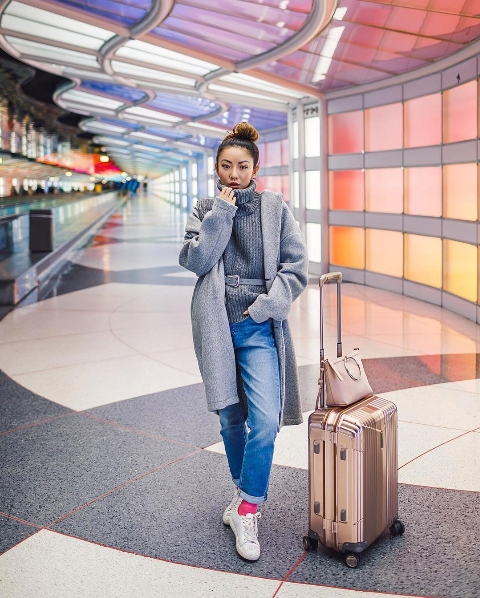 With gray sweater, gray knee-length coat, beige bag, loose jeans and white sneakers