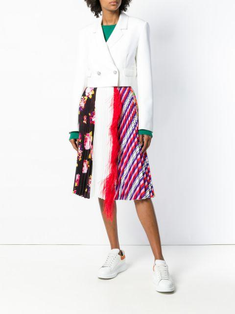 With green shirt, printed pleated skirt and white sneakers