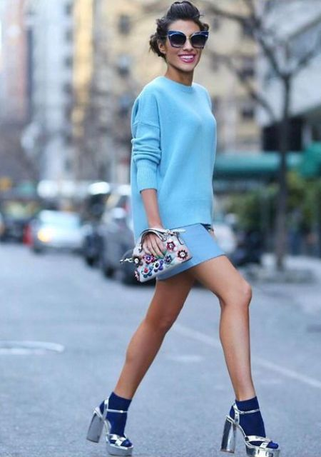 With light blue sweatshirt, mini skirt, embellished bag and silver shoes