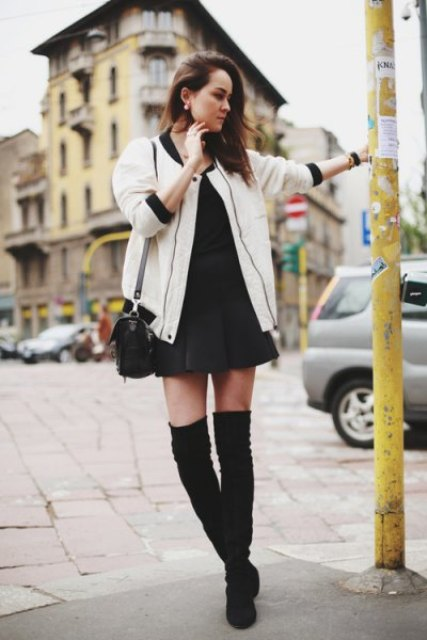 With mini pleated skirt, black shirt, bag and over the knee boots