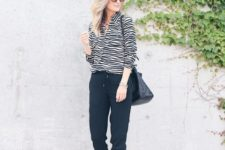 With navy blue jogger pants, black bag and zebra printed shoes