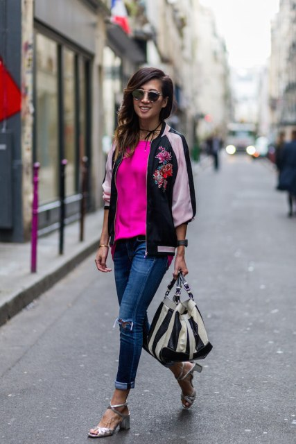 With pink shirt, distressed jeans, striped bag and silver sandals