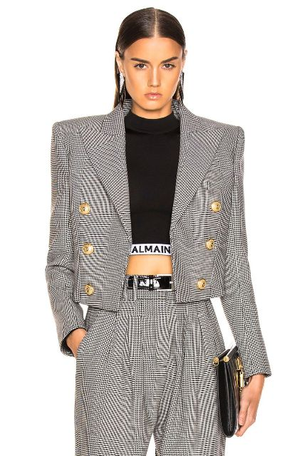 With printed high-waisted trousers, black belt, crop top and black clutch