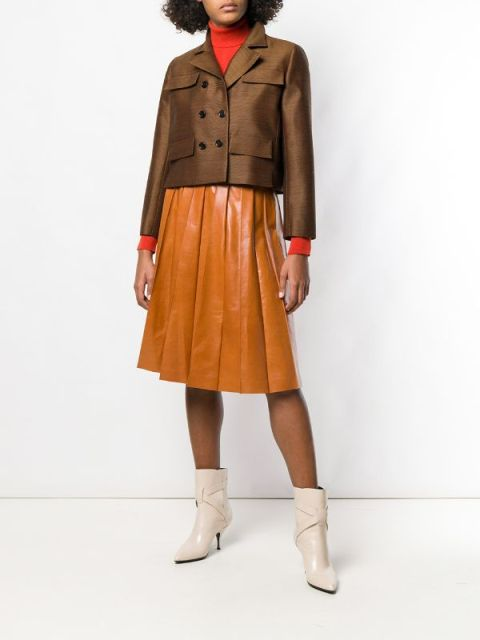 With red turtleneck, brown leather pleated skirt and beige ankle boots