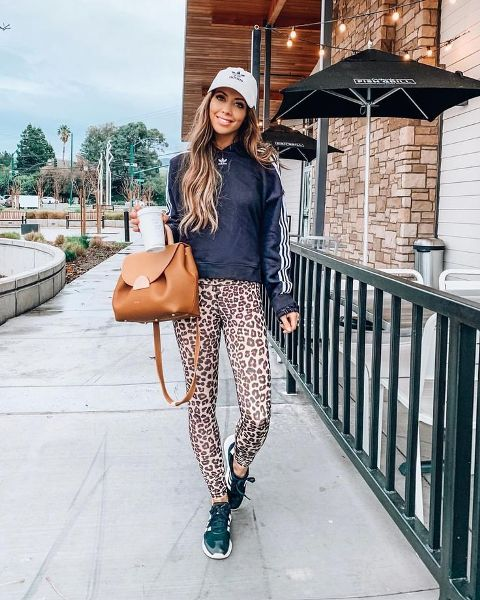 With sweatshirt, cap, brown leather bag and sneakers