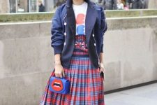 With t-shirt, navy blue jacket, checked pleated skirt, black pumps and printed bag
