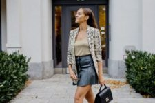 With top, black leather mini skirt, black bag and ankle boots