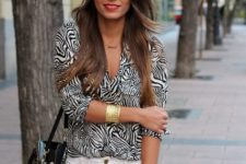 With white pants and black leather bag
