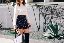 With white sweater, black tote bag and black over the knee boots