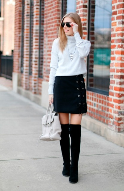 With white sweater, white bag and black high boots