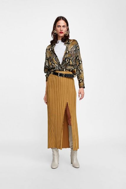 With white t shirt, yellow pleated maxi skirt, black belt and white high boots