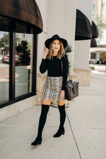 With wide brim hat, black shirt, over the knee boots and bag