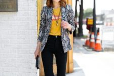 With yellow and red t-shirt, black pants, clutch and black pumps