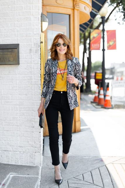 With yellow and red t shirt, black pants, clutch and black pumps