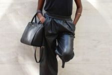 a black strap top, black leather bermuda shorts, white trainers and a black bag for a casual look