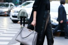a business look with a black top, lack leather cropped pants, silver shoes, a black coat and a grey bag