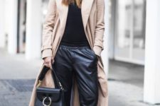 a casual outfit with a black turtleneck, black leather pants, white sneakers, a black bag and beanie and a tan trench