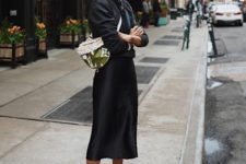 a catchy look with a black hoodie, a slip midi skirt, colorful sneakers and a bright bag