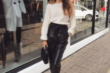 a chic and simple casual outfit with a white sweater, black leather high waisted pants, white sneakers and a black bag
