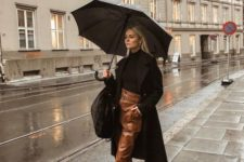 a chic look with a black turtleneck, brown leather pants, sock boots, a black coat and a bag