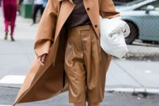 a chic minimalist look with a brown top, tan leather bermudas, black shoes, a brown trench and a white bag