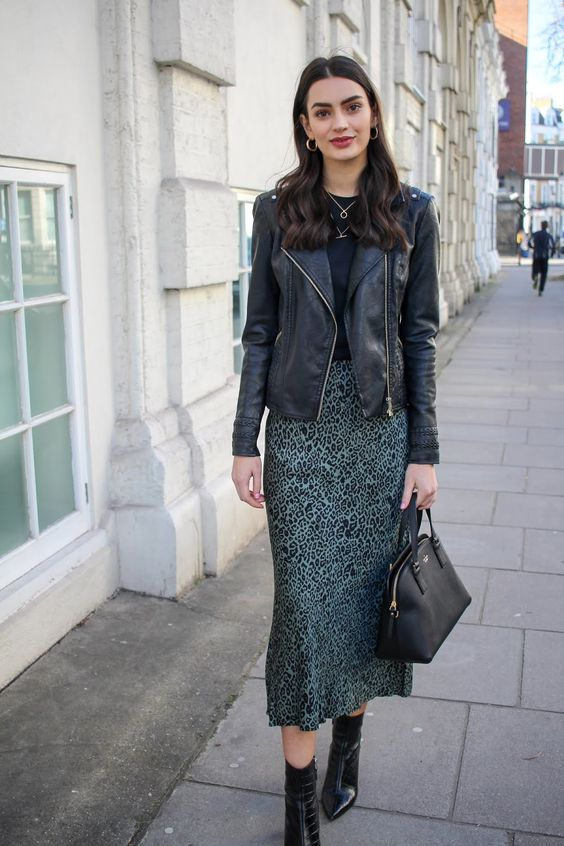 a dark look with a black tee, a green animal print slip skirt, black booties, a black leather jacket and a bag