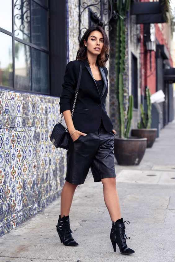 a gorgeous black outfit with a top, leather bermudas, a velvet tux blazer, black booties and a bag