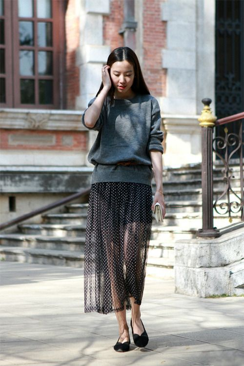a grey oversized sweater dress, a sheer polka dot skirt, black flats and a white clutch