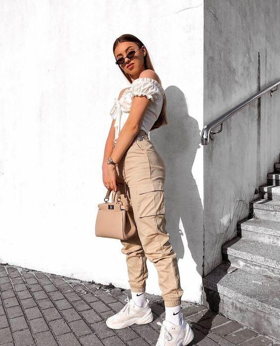 a hot outfit with tan cargo pants, a white off the shoulder top, white trainers and a tan bag