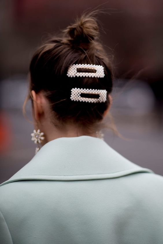 a messy bun accented with pearl hair clips and statement pearl earrings for an ultimate look
