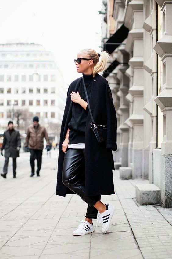 a monochromatic look with a black turtleneck, a white tee, white sneakers, a black coat and bag