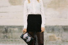 a monochromatic look with a white shirt, a black mini skirt, a black perforated skirt, black boots and a clutch